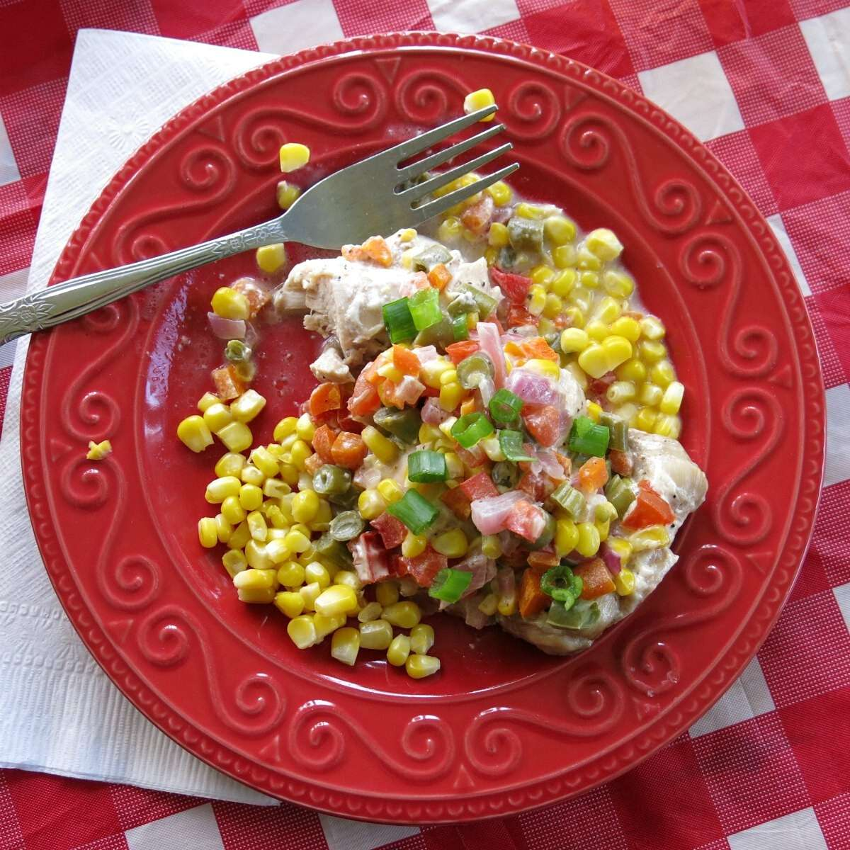Ranch chicken topped with vegetables on a plate with a fork.