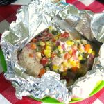Open ranch chicken foil packets with confetti vegetables on top.