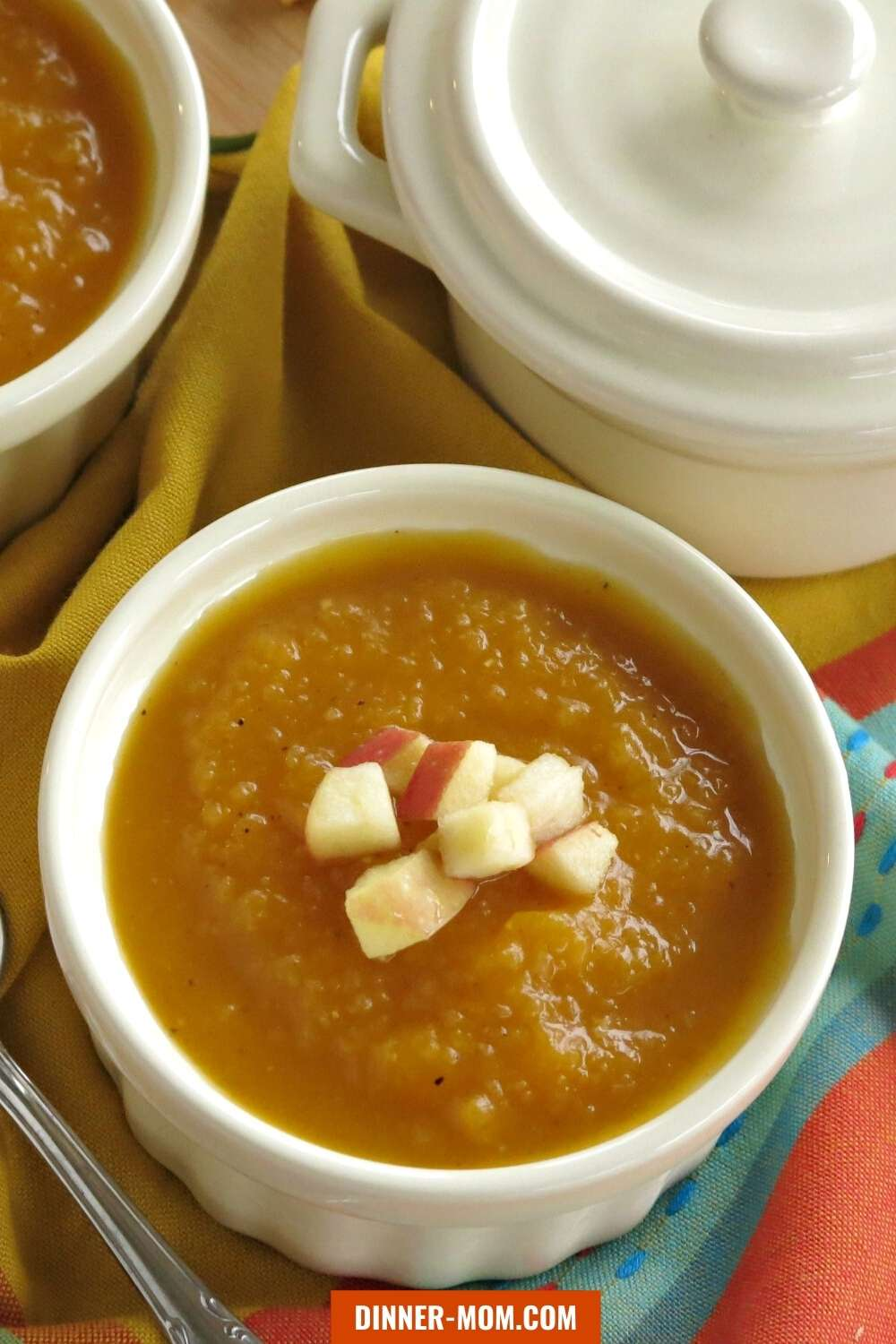Apple Butternut Squash Soup in a small bowl with covered bowl behind it.