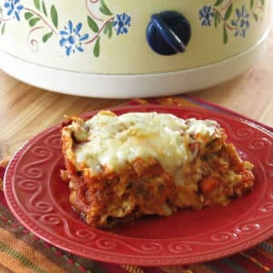 Slice of crock-pot vegetable lasagna on a plate in front of a slow cooker.