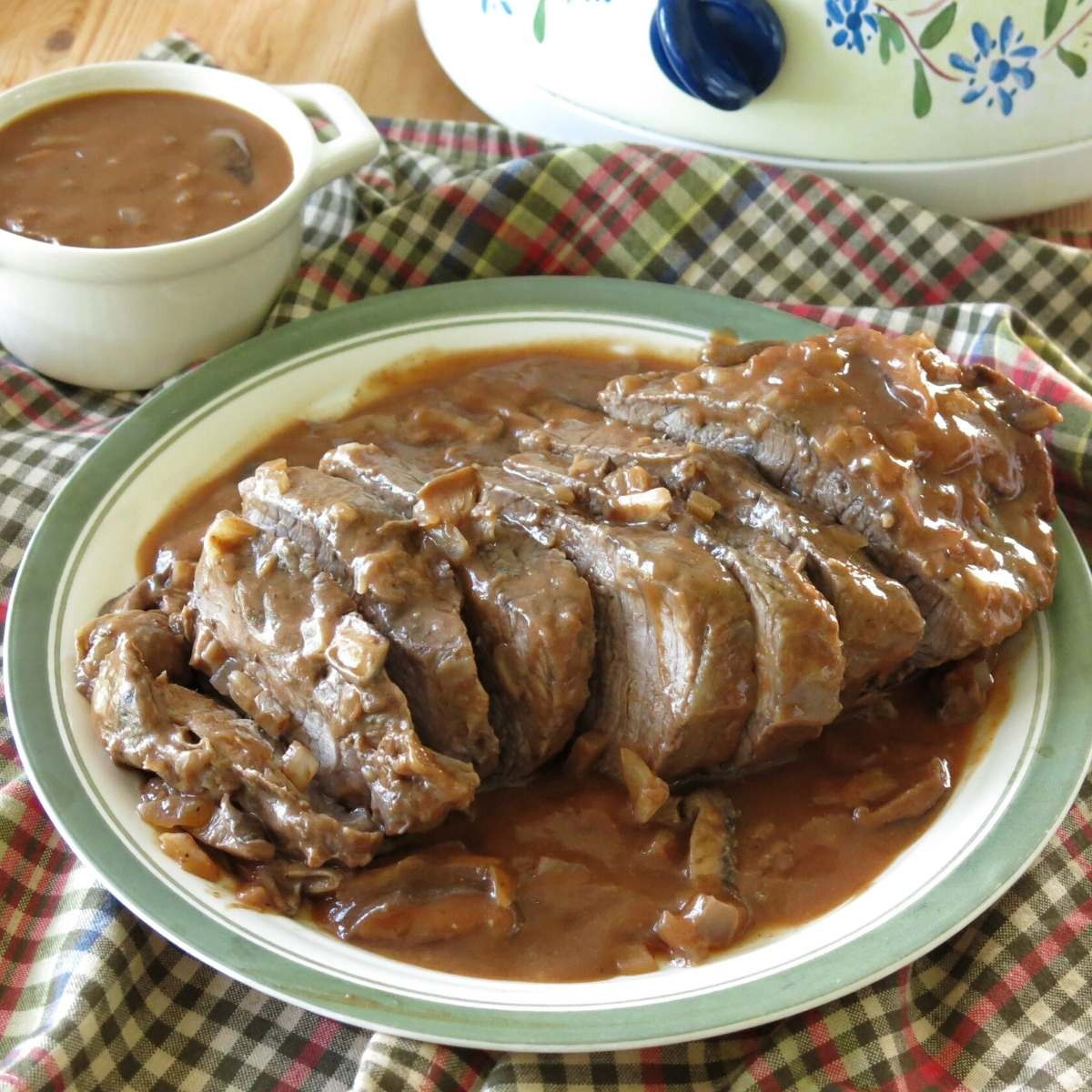 Sliced Beef Shoulder Roast with red wine mushroom sauce poured over the top.