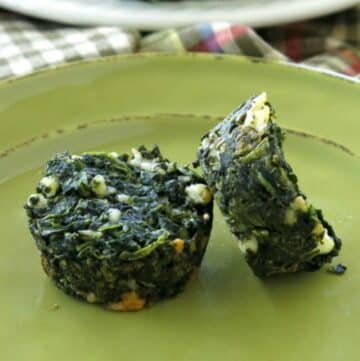2 spinach egg muffins with feta cheese on a green plate.