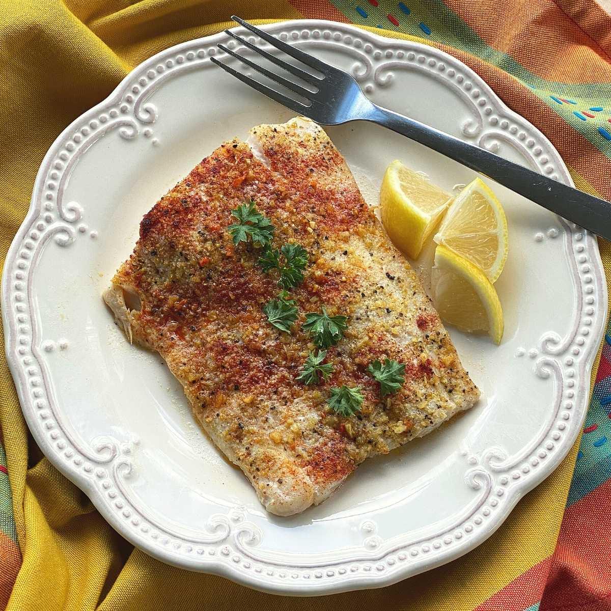 Filetto di corvina al forno con crosta di pepe al limone su un piatto con spicchi di limone e una forchetta.