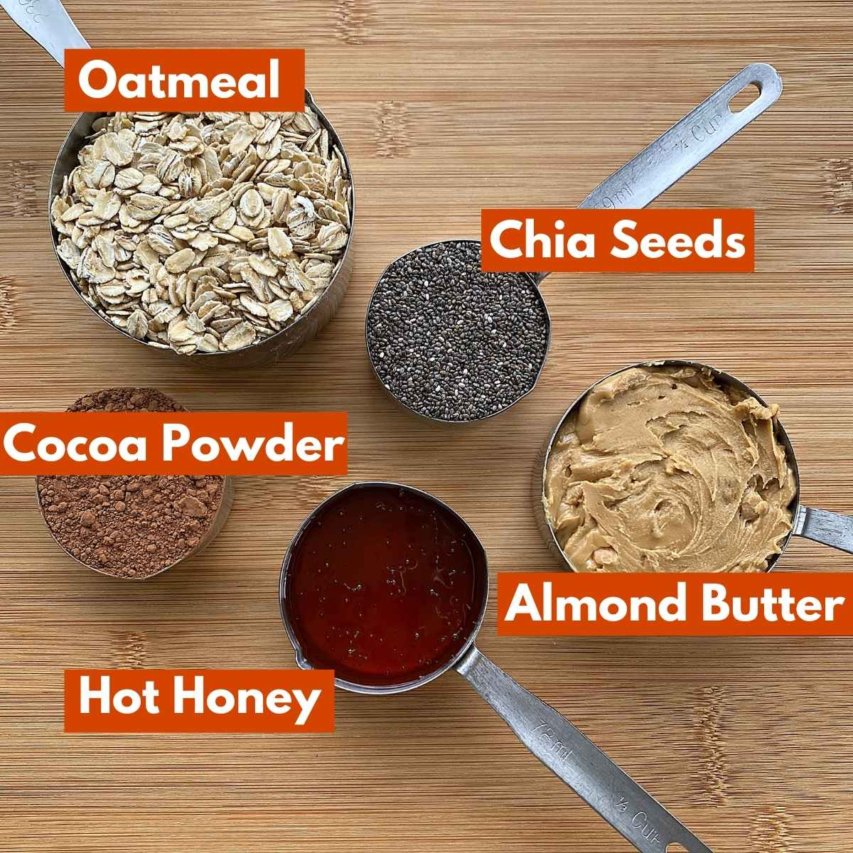 5 Ingredients in measuring cups with labels: oatmeal, chia seeds, cocoa powder, almond butter, hot honey.