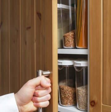 Hand opening the door of an organized pantry with decanted storage containers inside.