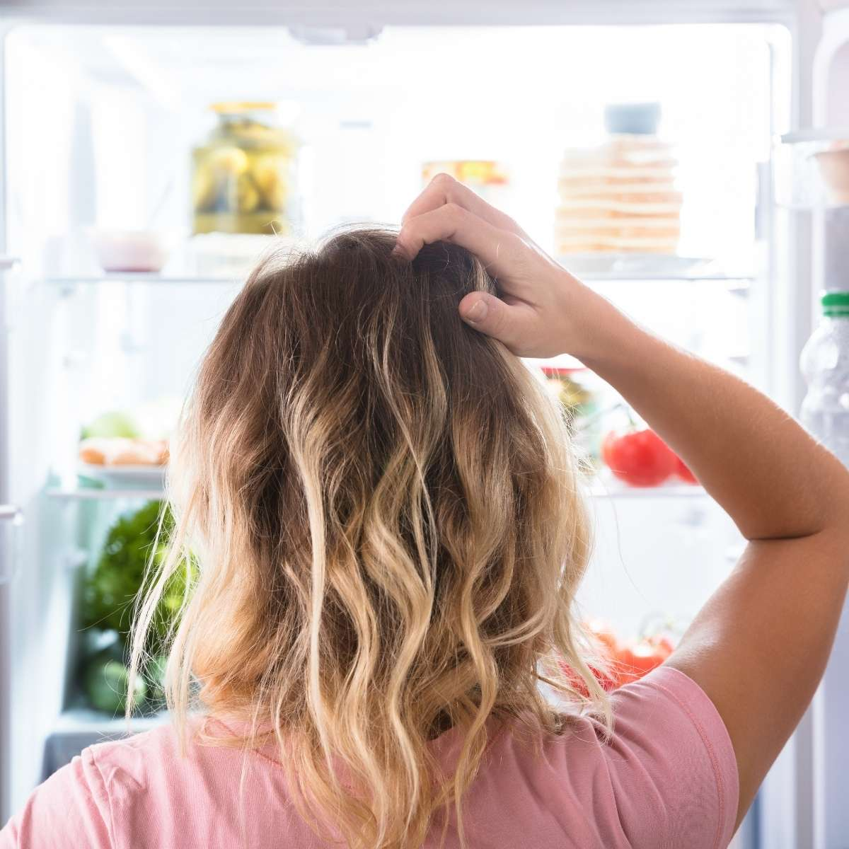 Person scratching that back of head looking into an organized refrigerator with the doors open.