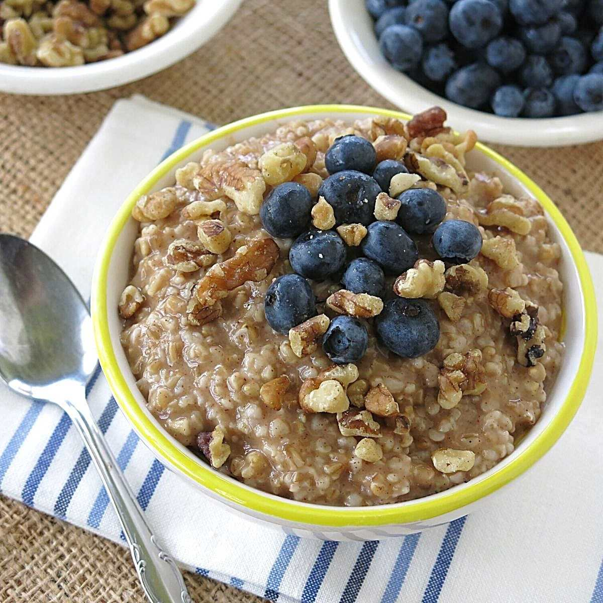 Bowl of slow cooker steel cut oatmeal with blueberries and walnuts on top and more blueberries in the background.