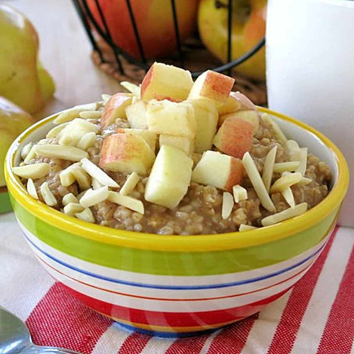 Bowl of slow cooker steel cut oatmeal in a bowl topped with apples and almonds.