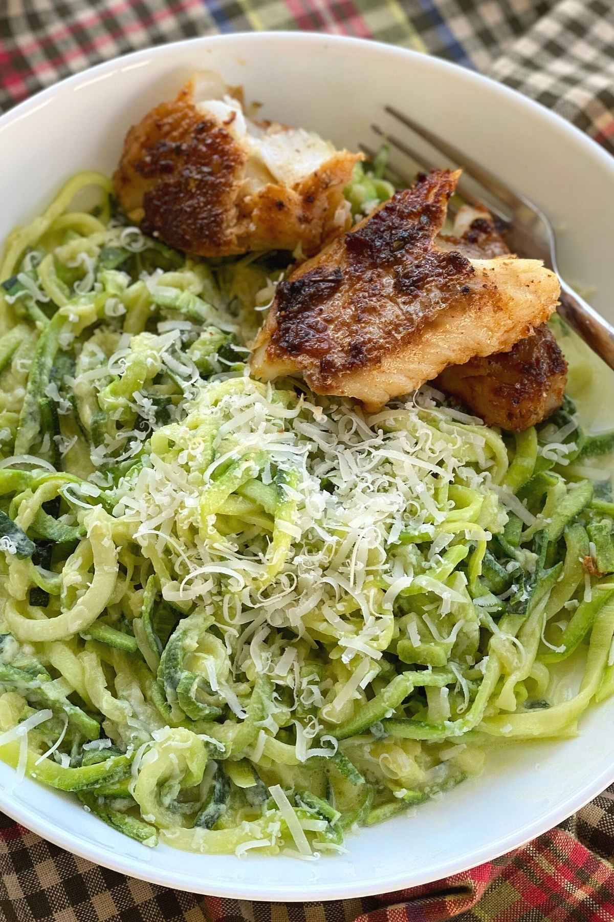 Fish with zucchini noodle alfredo in a bowl.