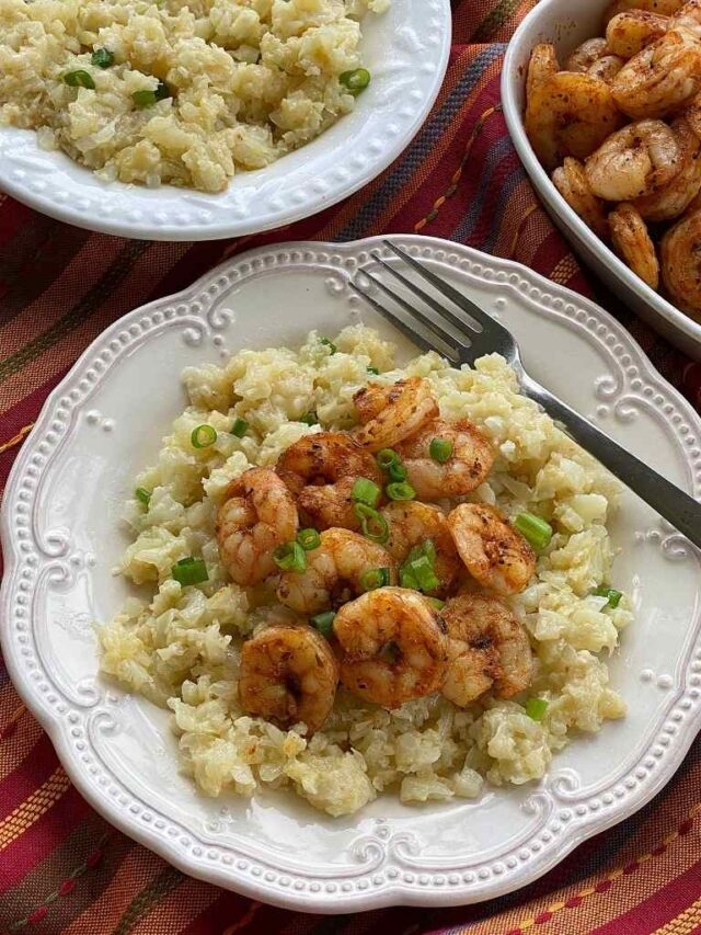 Cheesy Cauliflower Grits and Spicy Shrimp on a plate with bowls of grits and shrimp in the background.