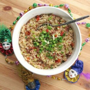 Easy Cajun Dirty Rice with sausage in bowl surrounded by Mardi Gras beads.