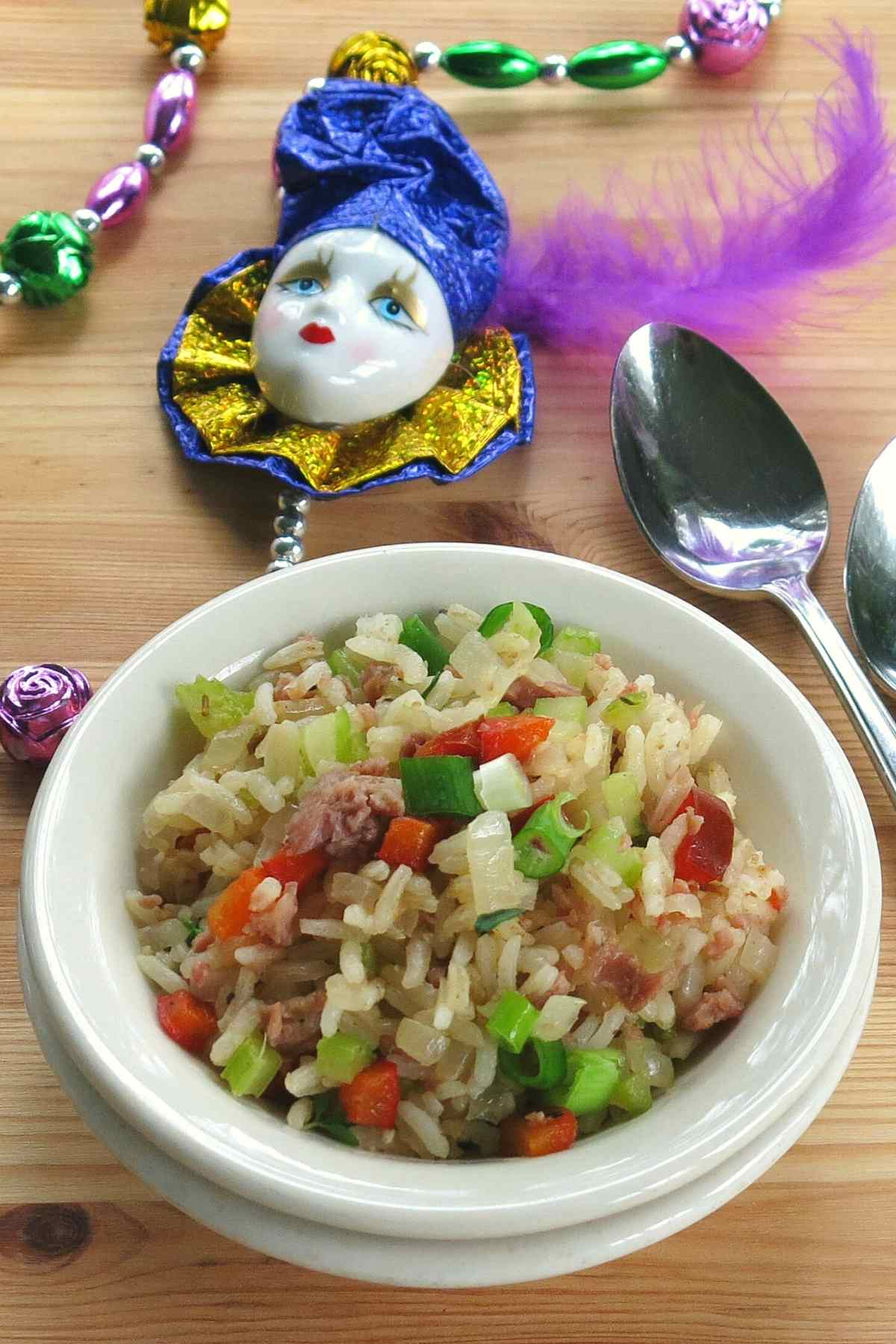 Side dish of recipe with spoons and Mardi Gras beads in the background.