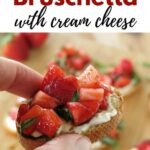 Hand holding strawberry bruschetta with cream cheese with title above it.
