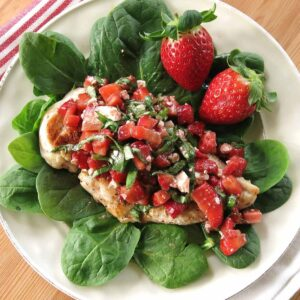 trawberry Chicken with an elegant bruschetta topping with basil and balsamic vinegar on a plate with spinach leaves and more strawberries in the background.