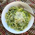 Bowl of zucchini noodle alfredo with a fork.