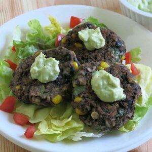 3 black bean cakes on a plate topped with avocado cream
