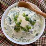 Bowl of cauliflower colcannon recipe with wooden serving spoon.