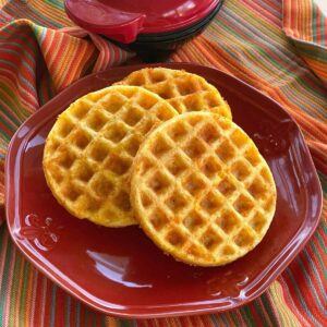 Keto chaffles on plate with Dash mini waffle maker behind it.