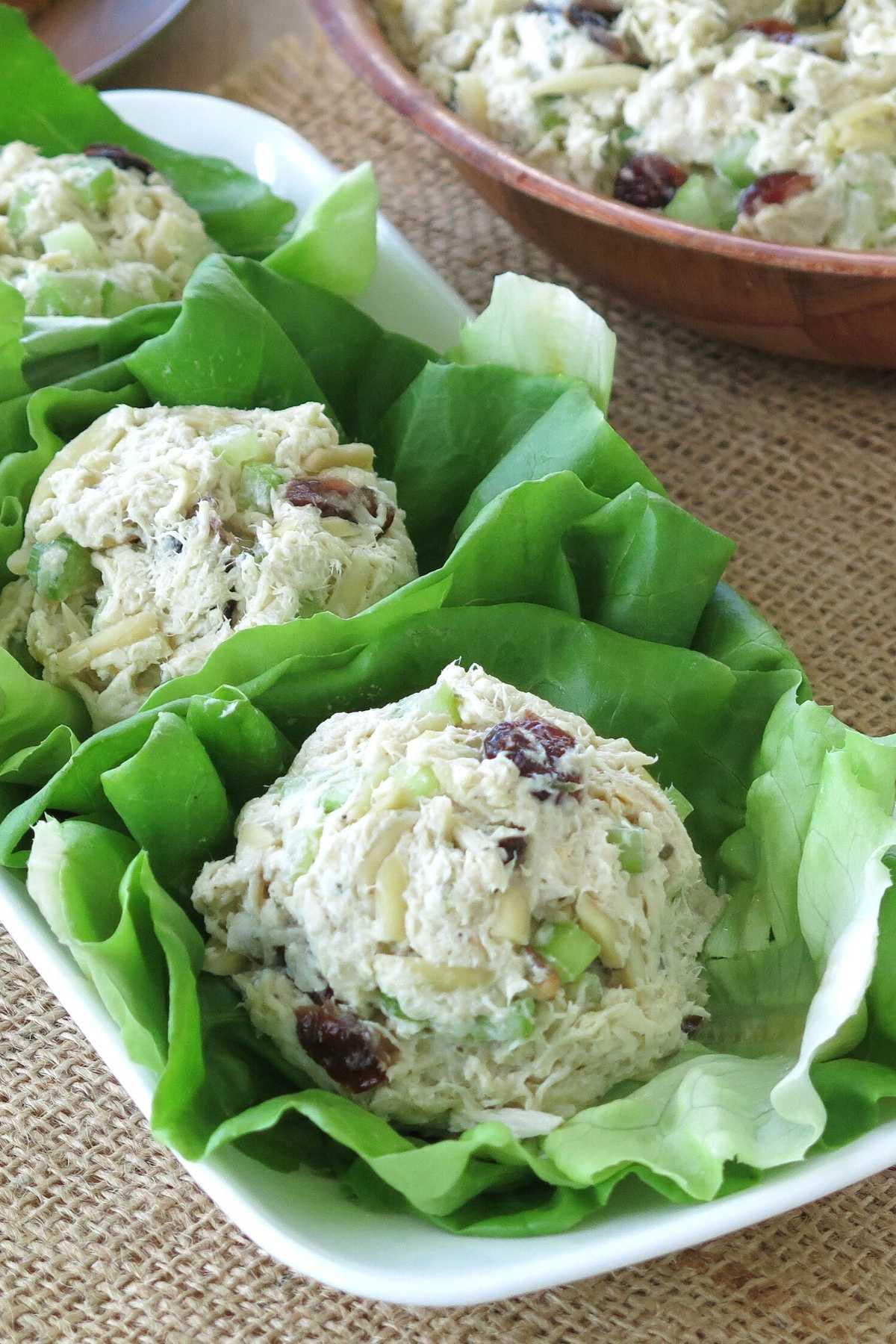 Scoops of crock-pot chicken salad on lettuce leaves on a platter.