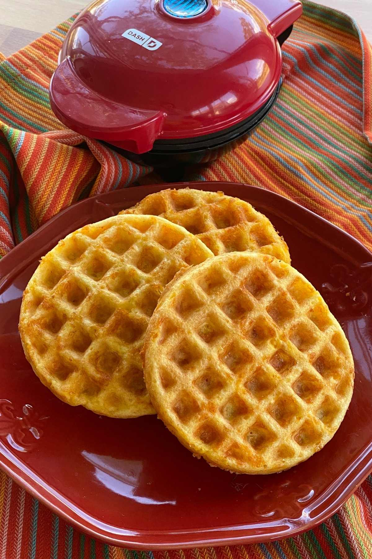Easy keto chaffles on a plate with a dash mini waffle maker behind it.