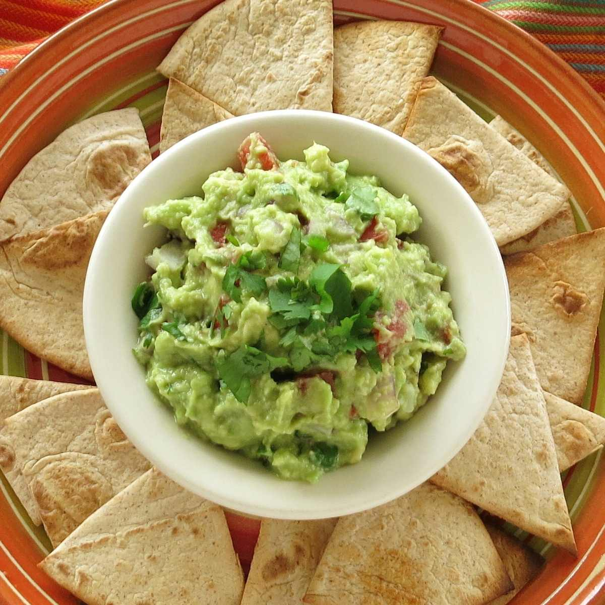 Guacamole in a bowl surrounded by homemade low-carb flour tortilla chips.