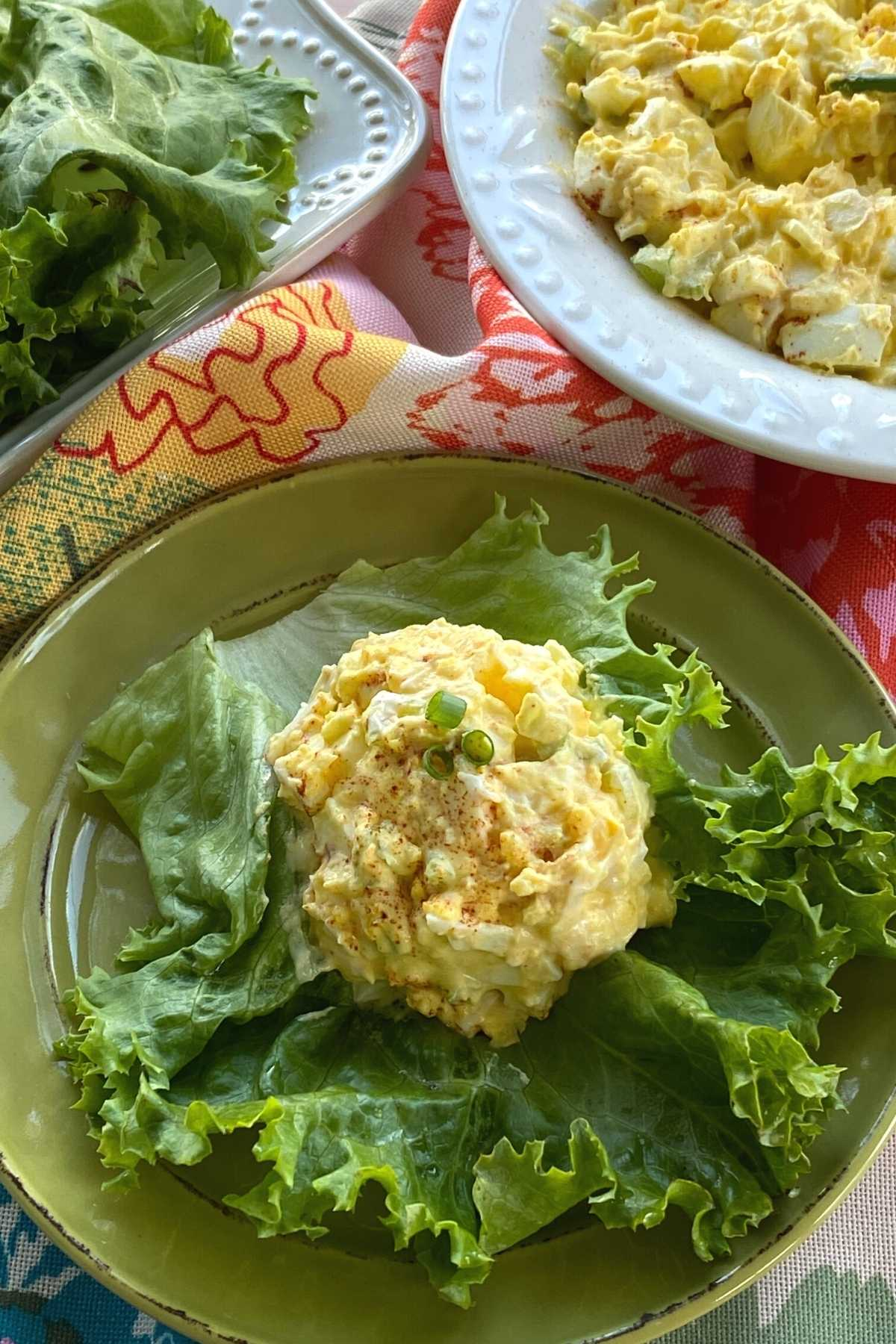 Scoop of low-carb egg salad on a large lettuce leaf with serving bowl and more leaves behind it.