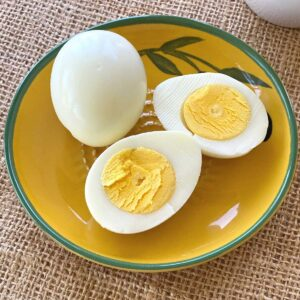 2 hard boiled eggs cooked in a Ninja Air Fryer. 1 is whole, the other cut in half.