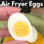 Hand holding half an egg with yolk with air fryer behind it.