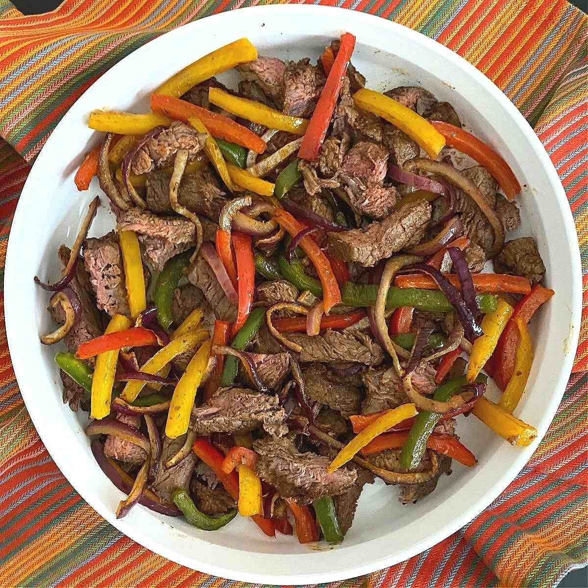 Air fryer steak fajitas with bell peppers and onions in a serving dish.