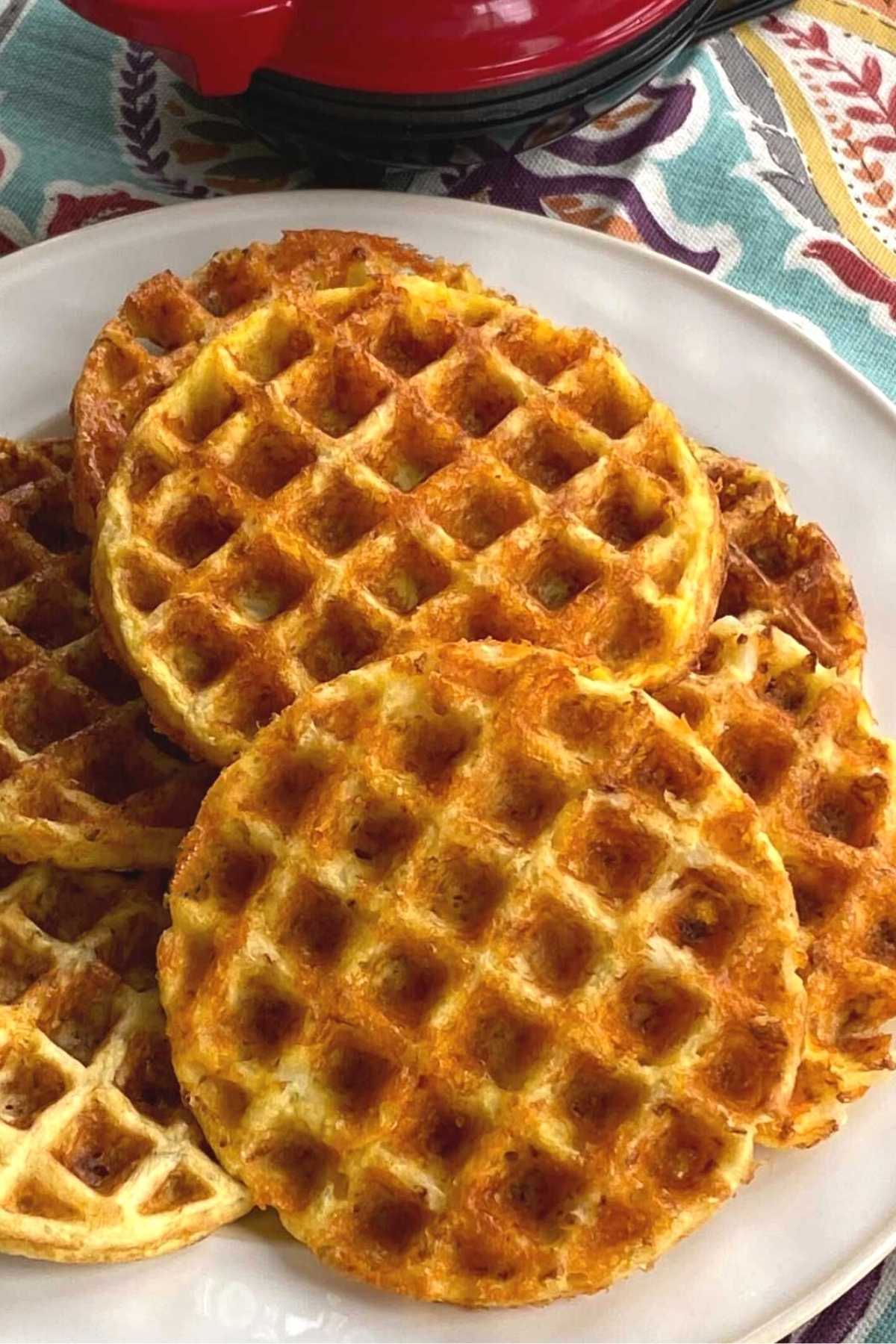 Cauliflower chaffles scattered on plate with Dash waffle iron behind it.