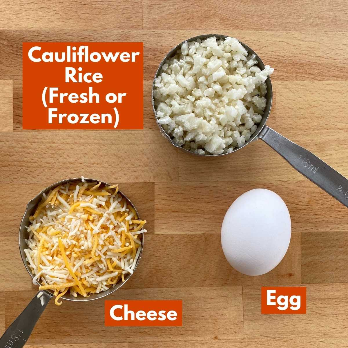 Ingredients to make recipe: cauliflower rice, egg and shredded cheese on cutting board.