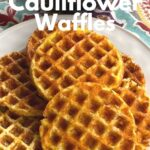 Keto cauliflower waffles on plate with Dash waffle maker behind it.