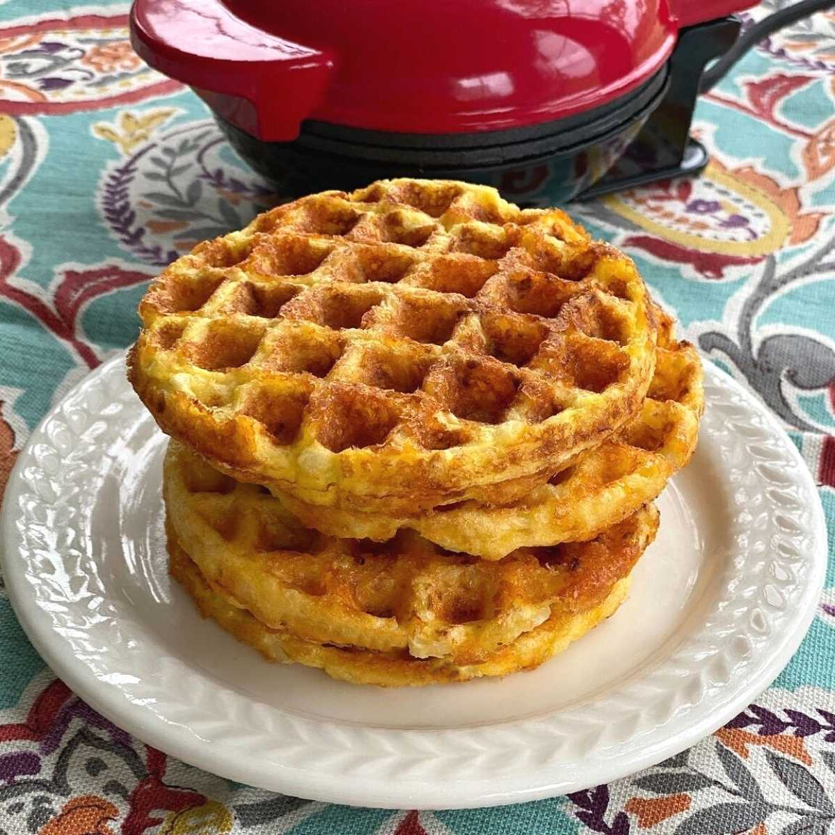 Cauliflower waffles stacked on a plate in front of waffle maker.