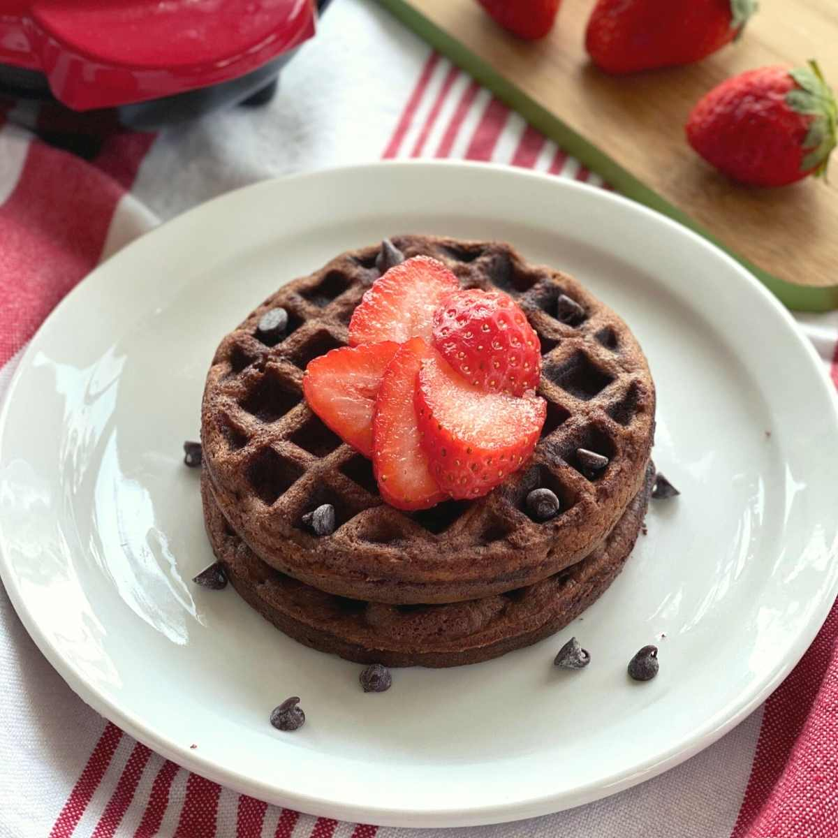 2 chocolate chaffles on a plate with strawberries and chocolate chips on top and a Dash waffle iron behind them.