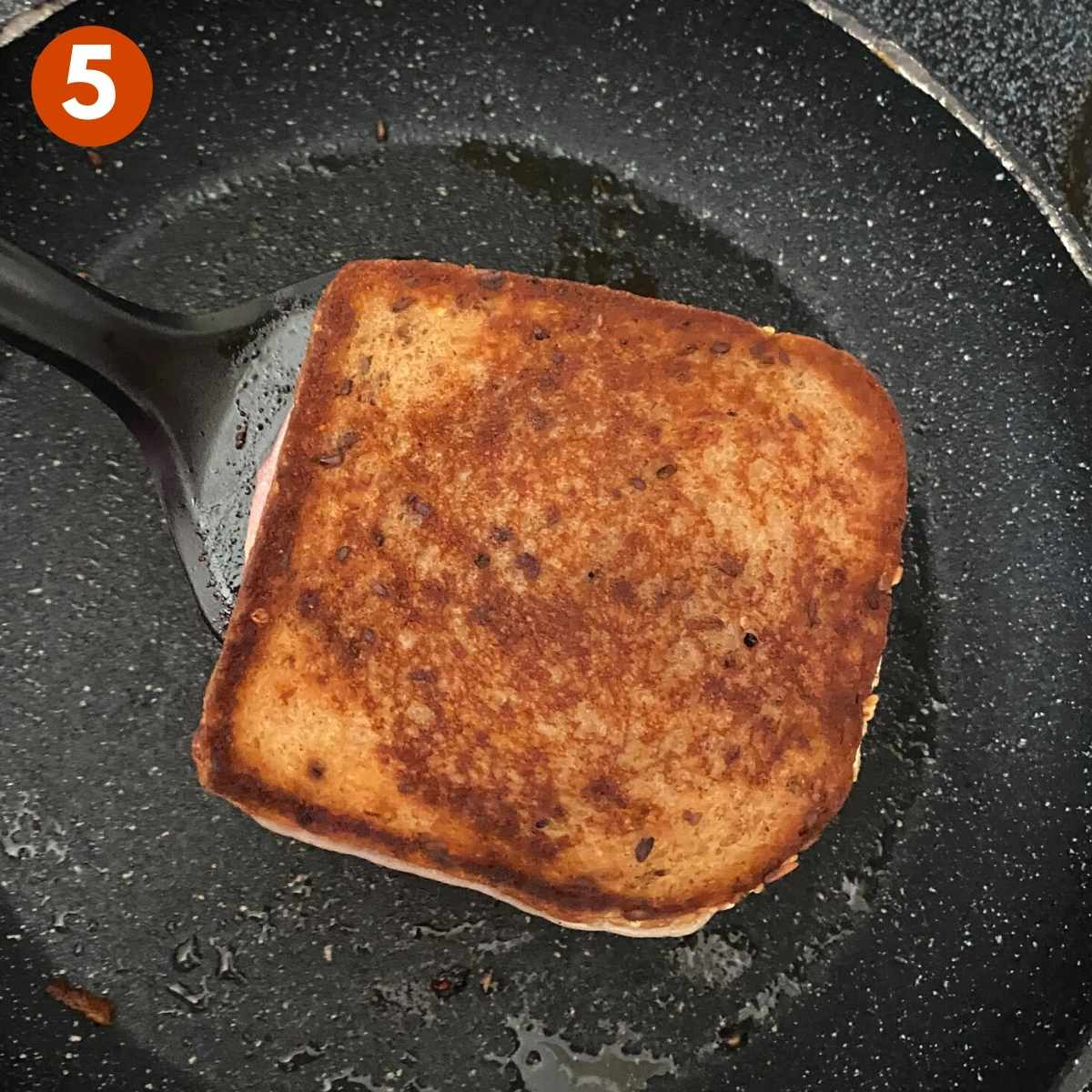 Step 5 Cooked grilled cheese on spatula in pan.