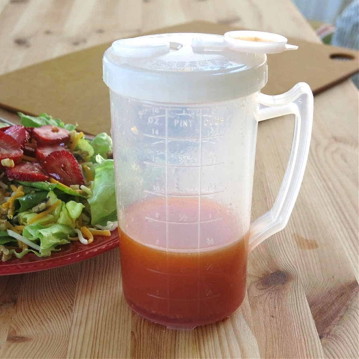 Red wine vinegar dressing in plastic container with measurement markings with strawberry salad next to it.
