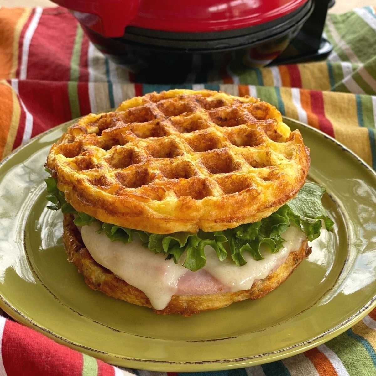 Ham and cheese sandwich with chaffle bread on the top and bottom.