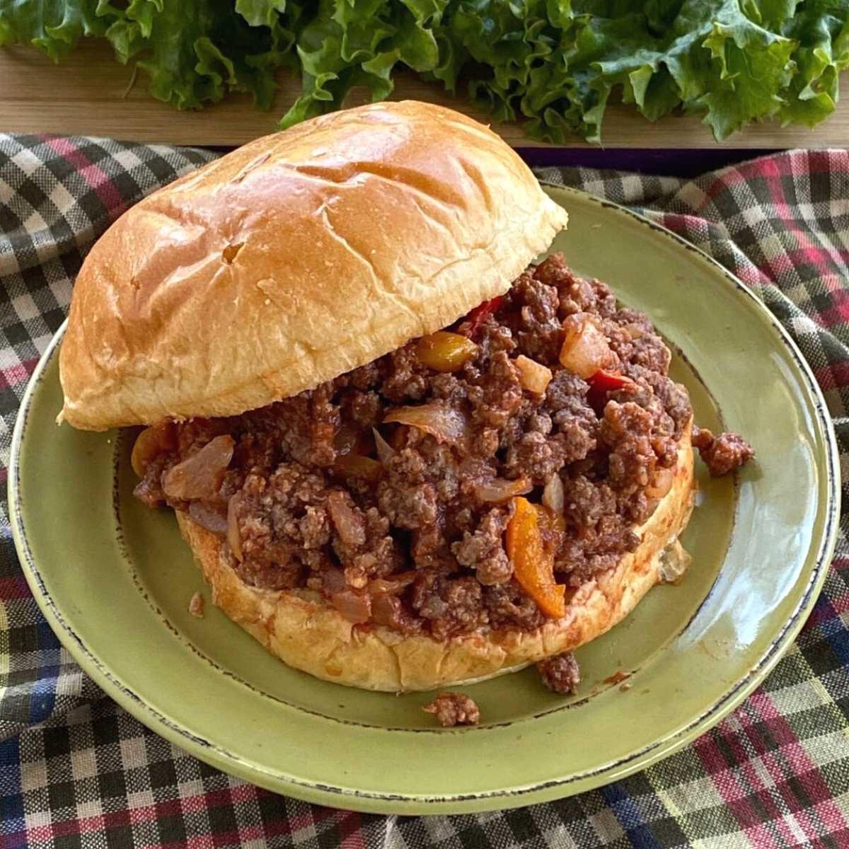 Sloppy Joe on brioche hamburger bun on plate with lettuce leaves behind it.