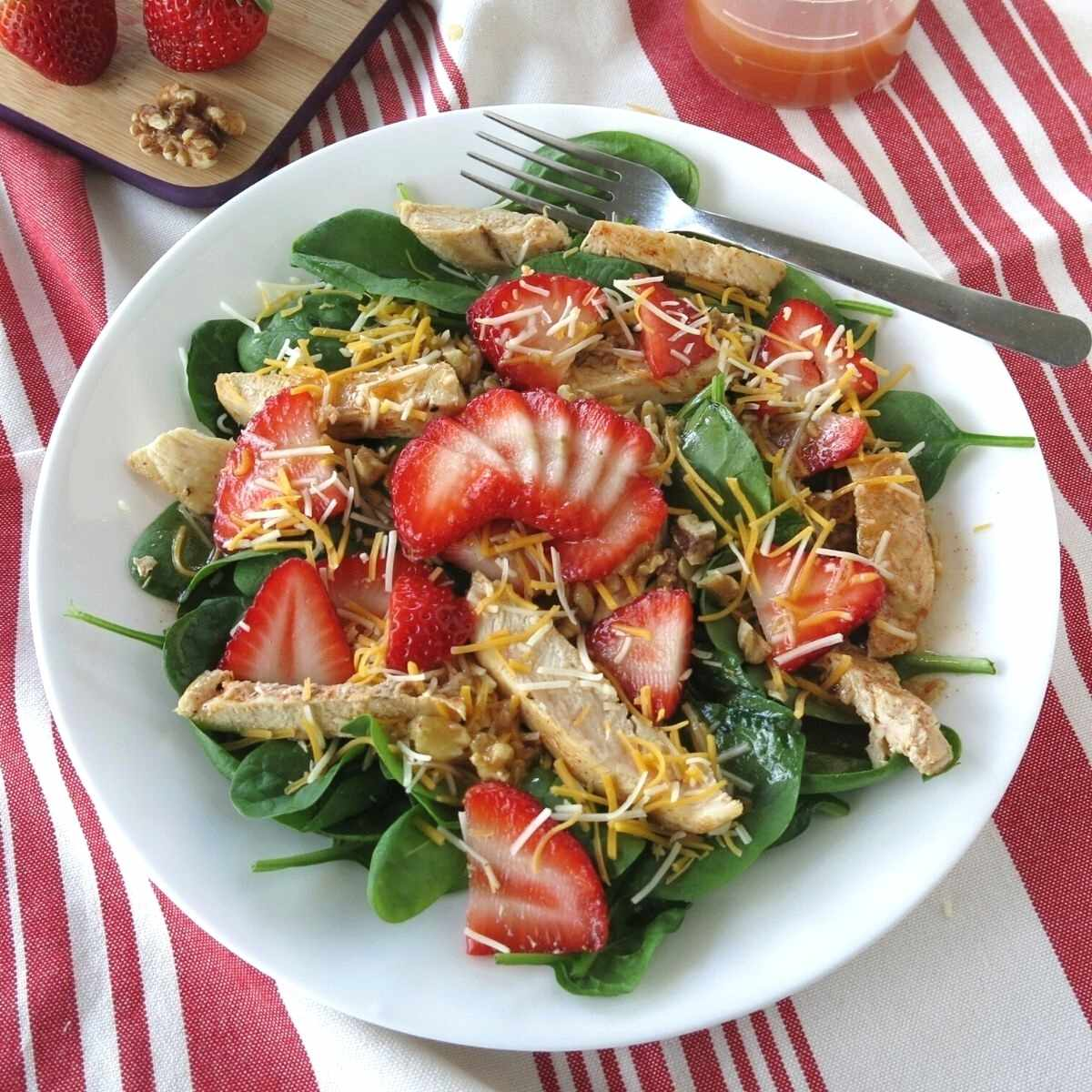 Spinach salad with strawberries, walnuts, cheese and chicken on a plate with a fork.