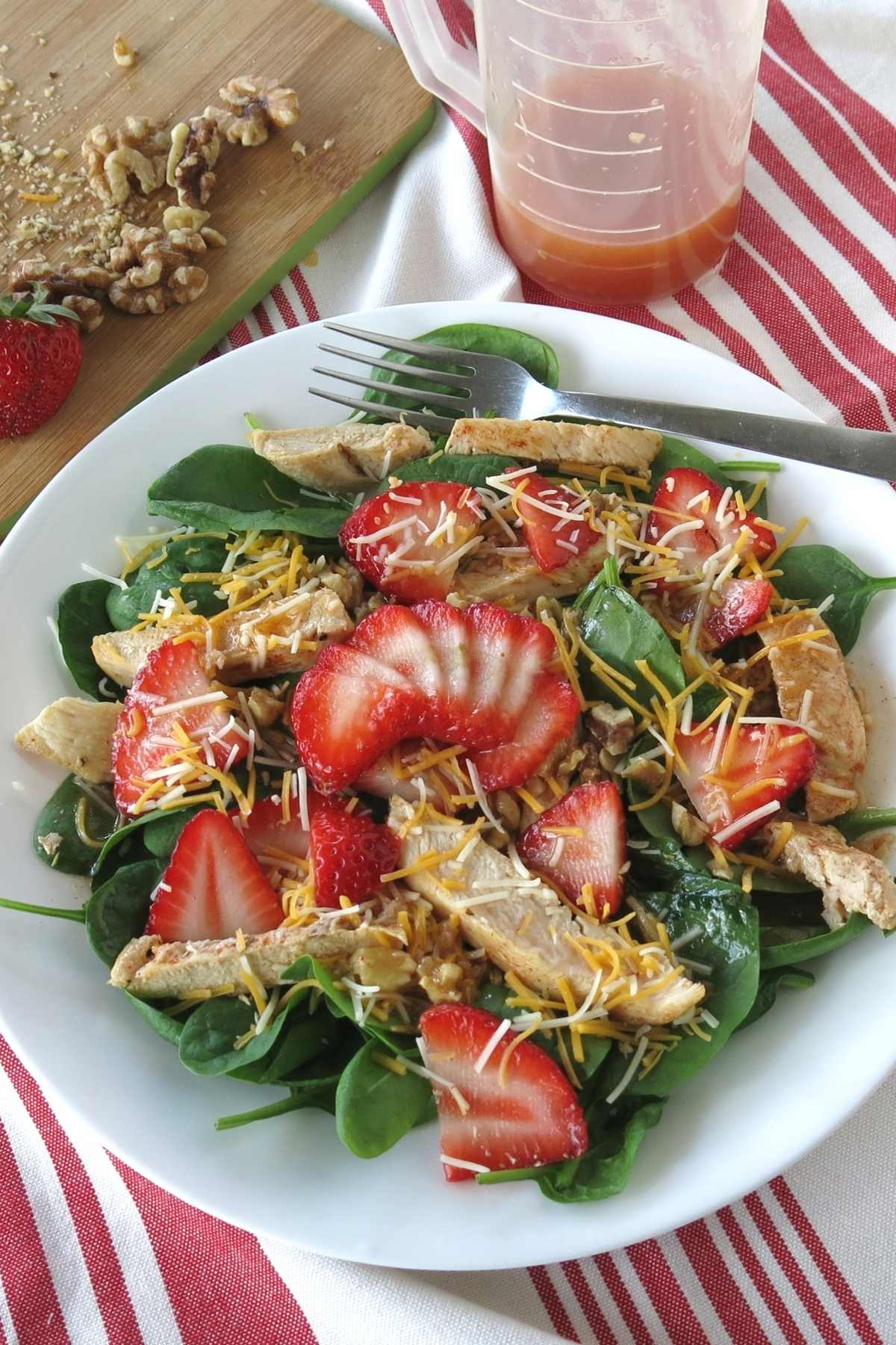 Assembled Strawberry Salad on plate with dressing, walnuts and strawberries in the background.
