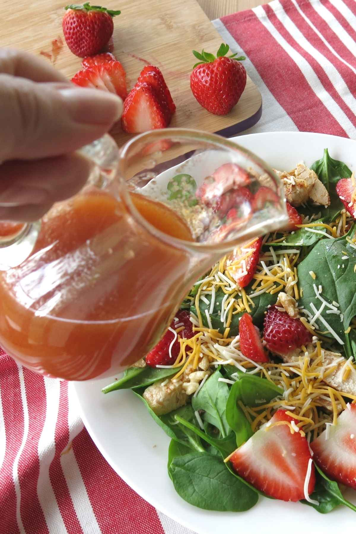 Hand pouring sweet red wine vinaigrette dressing over strawberry salad.