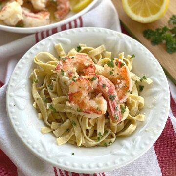 Red Argentine Shrimp Scampi over a bowl of pasta.