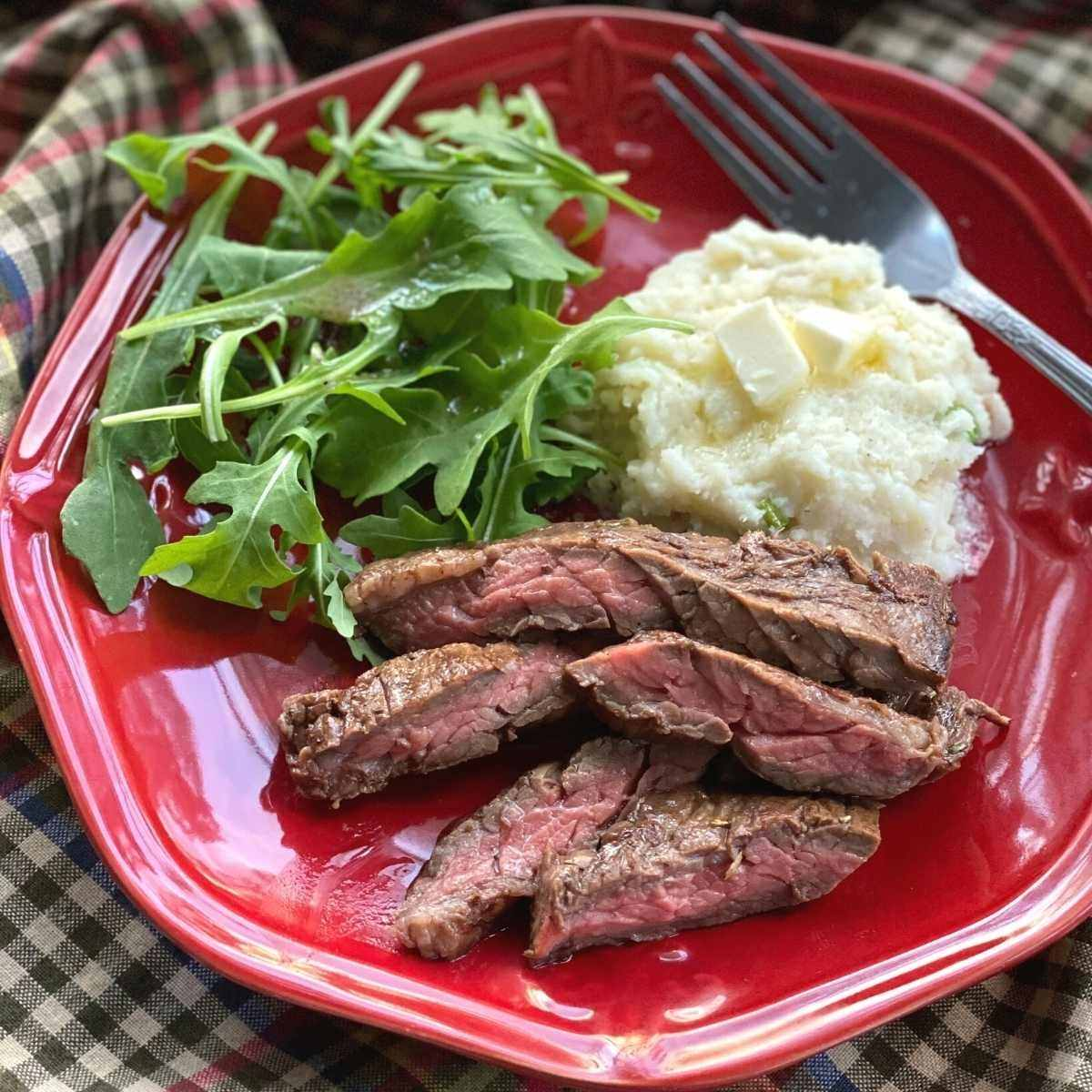 Slices of bavette steak on a plate with mashed cauliflower and arugula.