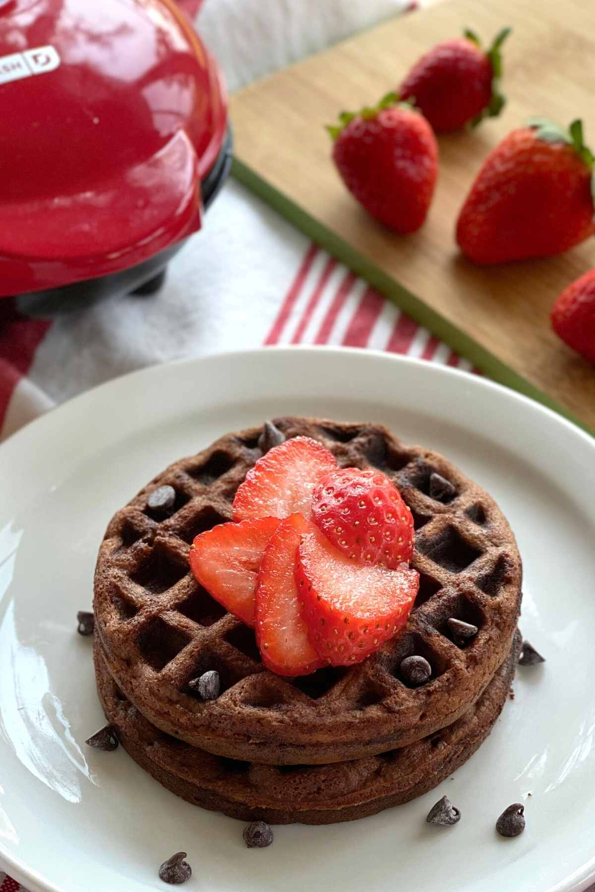Plate with 2 Chocolate Waffles with waffle iron and strawberries behind it.