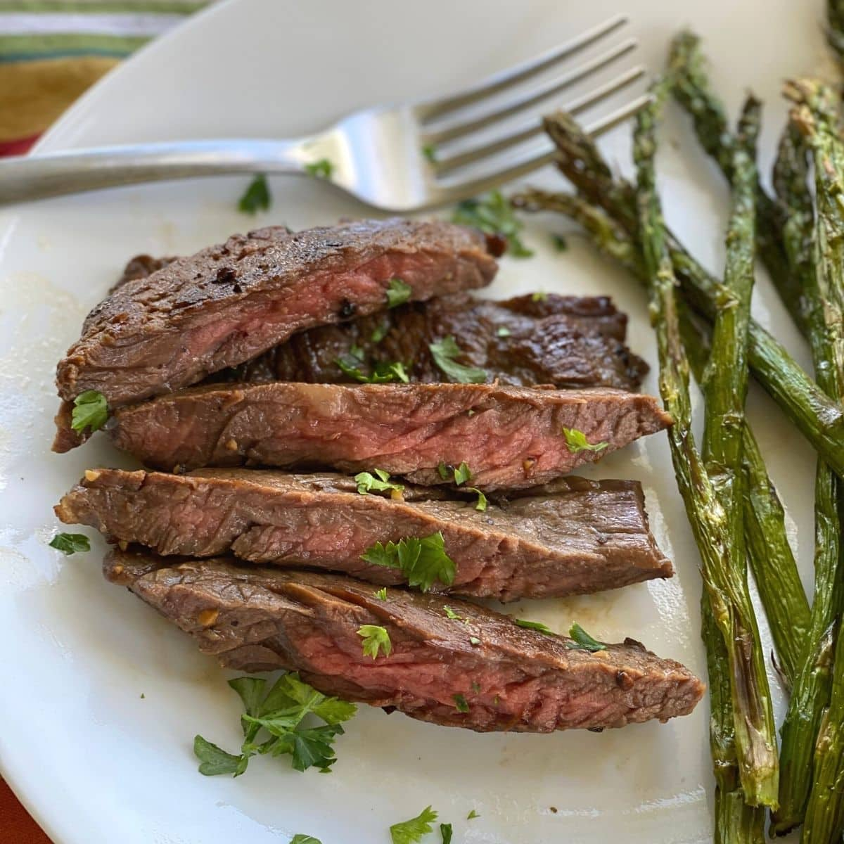 Cooked flap steak on plate with asparagus and fork.