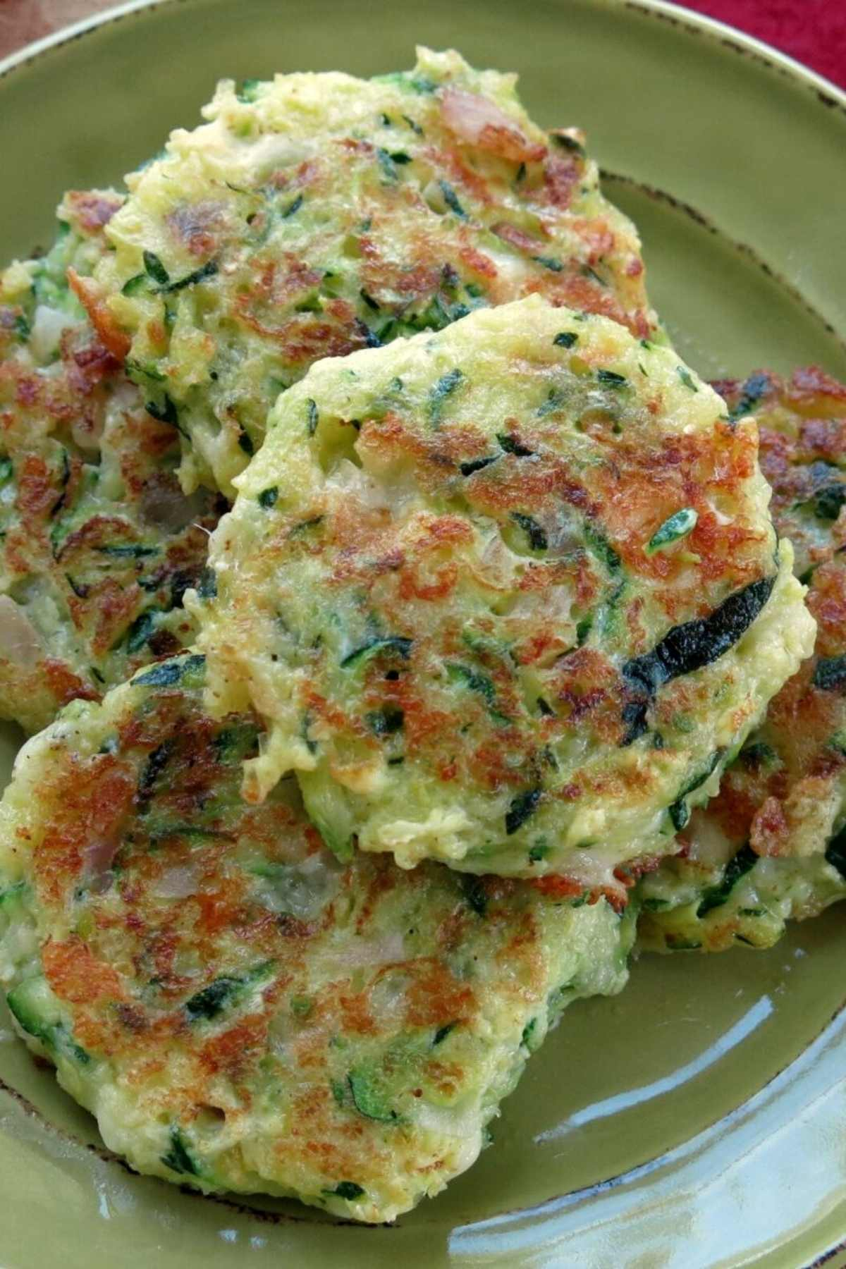 Healthy zucchini cakes piled on a plate.