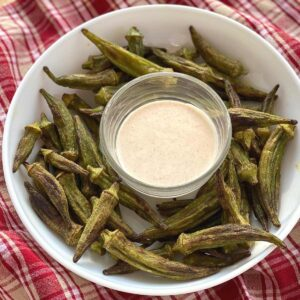 Okra fries on a plate surrounding a bowl with aioli dipping sauce.