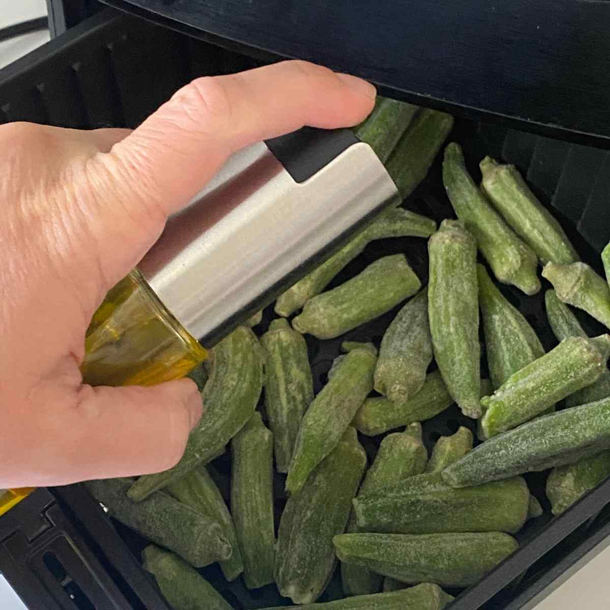 Hand holding olive oil mister over okra pods in an air fryer.