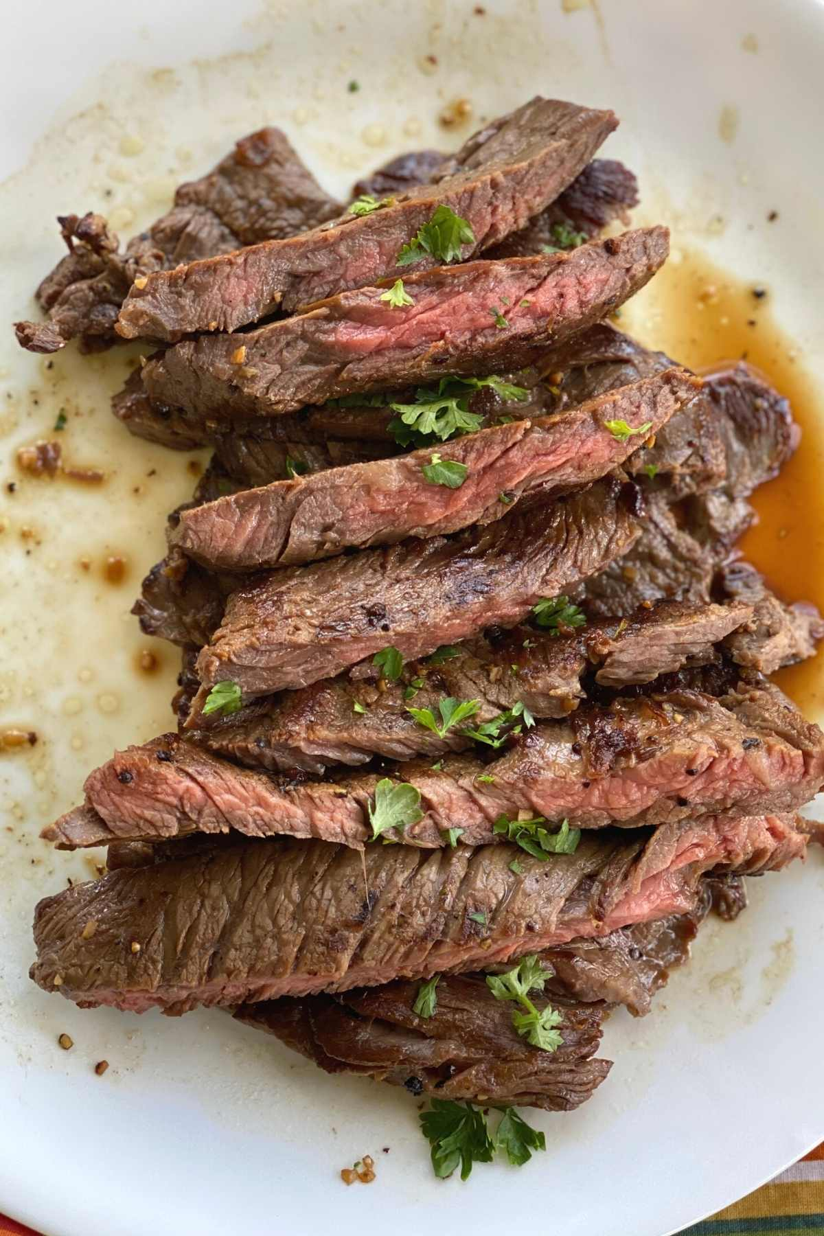 Slices of steak bavette piled on a plate and topped with parsley.