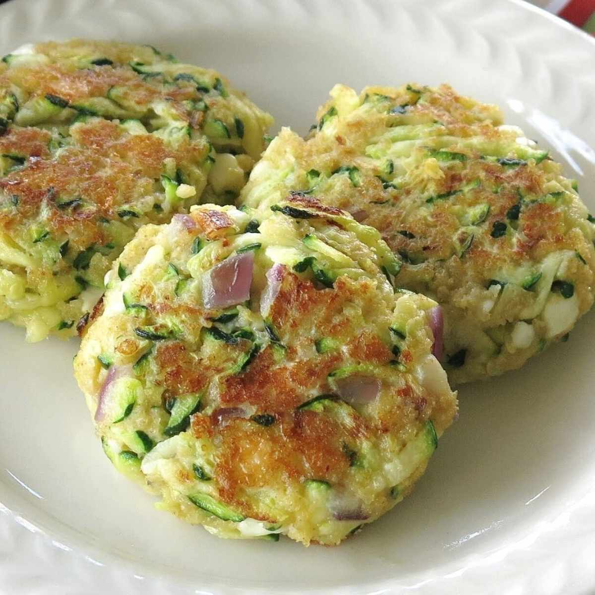 Three zucchini cakes with feta cheese on a plate.